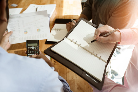 appropriately: Business colleagues meeting to determine their duties to summarize annual performance in the companys meeting room. The documents, business contracts placed on a wooden table. Stock Photo