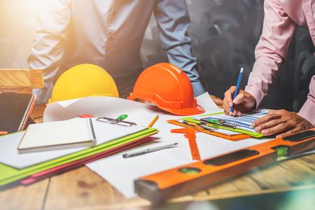 El trabajo en equipo del ingeniero estructural discutiendo el trabajo duro en la oficina en el concepto de la estructura de edificio del proyecto de construcción mundial.