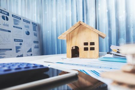Huis en onroerend goed te koop concept, houten huis speelgoed op kantoor bureau.