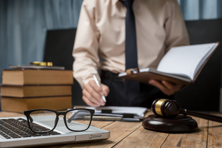 Business lawyer working hard at office desk workplace with book and documents. Archivio Fotografico