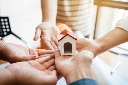 Teamwork of architectural engineer consulting on the creation of a model home, hands pointing to mini house toy model. Stock Photo