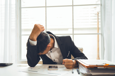 disheartened: Asian male businessman professional lawyer is tired and migraine headaches during hard work in the attorney general office to fight the court case that will be held next week. Stock Photo