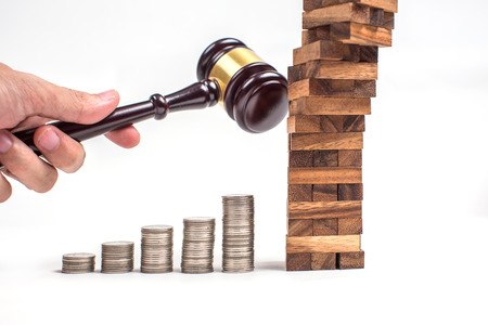 Business risk on wood jenga toy game with man hand and gavel destroy. Stock Photo