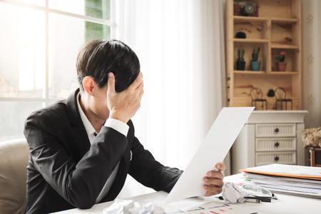 De Aziatische mannelijke zakenman professionele advocaat is vermoeid en migrainehoofdpijnen tijdens het harde werk in het procureursalgemene bureau om de rechtszaak te bestrijden die volgende week zal worden gehouden. Stockfoto