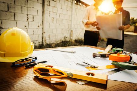Ein Schreibtisch mit Ingenieuren, die den Bereich für die Grundsteinlegung für energiesparende Häuser und Rohstoffkosten untersuchen.