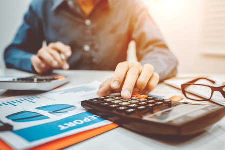 Young business man inspector in financial report of secretary making and counting calculator in office at home. Stock Photo