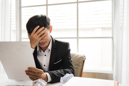 Asian male businessman professional lawyer is tired and migraine headaches during hard work in the attorney general office to fight the court case that will be held next week. Stockfoto