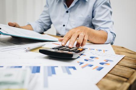 Comptable de l'homme d'affaires utilisant la calculatrice pour calculer le prêt d'impôt de l'argent de bugget.