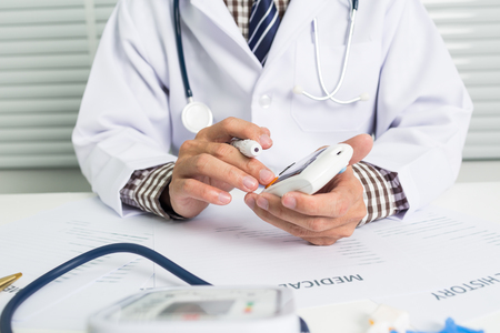 Young doctor with blood glucose monitor in general clinic.