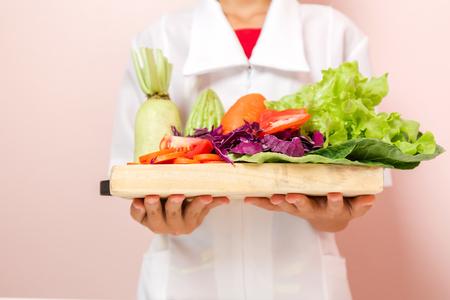 栄養士が消費者におすすめの健康野菜のトレイを持って立っています。