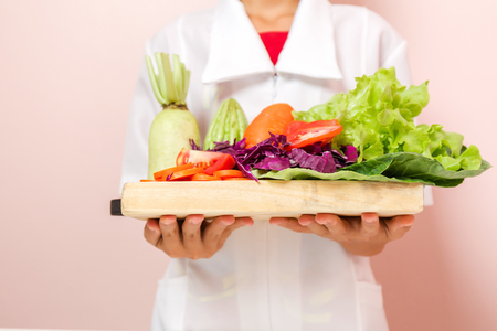 Nutritionist standing holding a tray of healthy vegetables recommended to consumers. Banque d'images