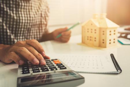 Młody biznesmen robi kalkulator kosztów finansowania w pracy w biurze domowym.