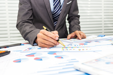 Bankers are recording financial information and balance sheet of the company to analyze the loan approval.