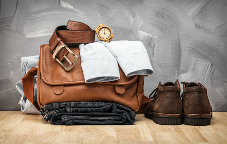 Asian vintage style men clothing and jeans and bag put on wooden table and loft concrete wall texture background.