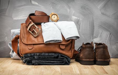 La ropa y los vaqueros y el bolso asiáticos del estilo del vintage del vintage pusieron la tabla de madera y el fondo de la textura de la pared del hormigón del desván. Foto de archivo