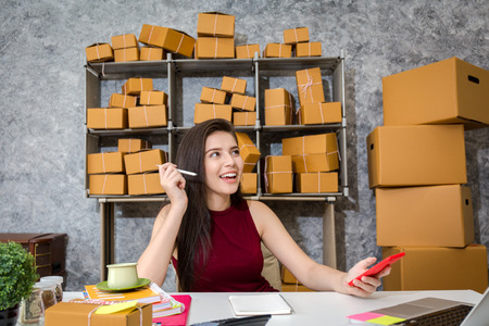 Young business owner as online freelancer checking the box and check the customer list. Stock Photo