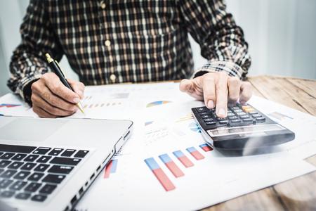 Les hommes calculent l'impôt sur le revenu des particuliers pour envoyer des informations aux agences gouvernementales. Utiliser un ordinateur portable et une calculatrice. Banque d'images
