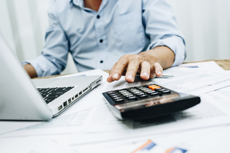 Business man accountant using calculator to calculating bugget money tax loan.