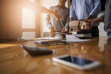 Geschäftstreffen von Immobilienmaklern und Unternehmenspräsidenten, um ein Modell für den Bau einer Wohnsiedlung in Schrift und Präsentation an staatliche Organisationen auszuwählen.