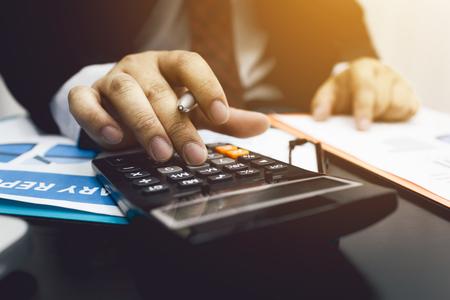 Contador do homem de negócio que usa a calculadora ao empréstimo fiscal do cálculo do dinheiro do bugget. Foto de archivo