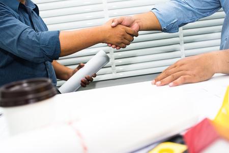 엔지니어 및 계약자의 악수 집을 짓는 계약에 서명.