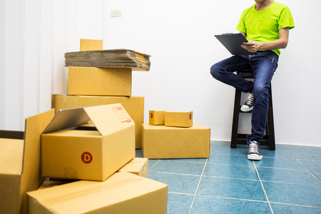 Young man as SME start up own business with box, work at home product delivery and checking order of customer of small business entrepreneur.