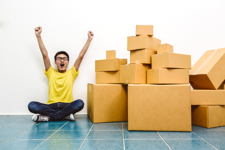 Asian man winner success as SME start up entrepreneur owner business with cardboard packaging box and delivery service.