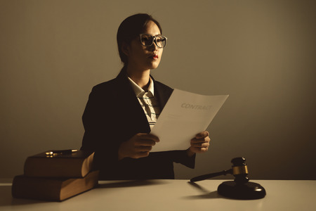Female lawyers are sitting at the table, vintage style, low key lighting, she is asian nationality.