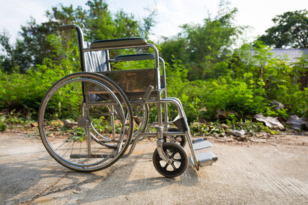 Wheelchair on the concrete road, outdoor nature object. Stock Photo