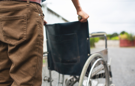 Close up empty wheelchair outdoor with male nurse walking forward. Stok Fotoğraf