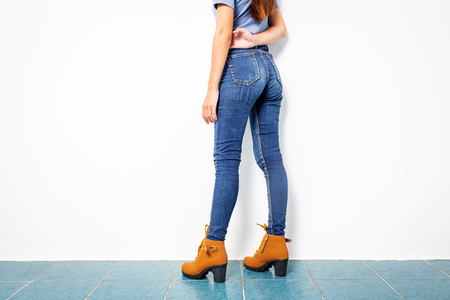 Young Asian 20s girl with jeans sexy leg with brown shoes fashion on white wall background.