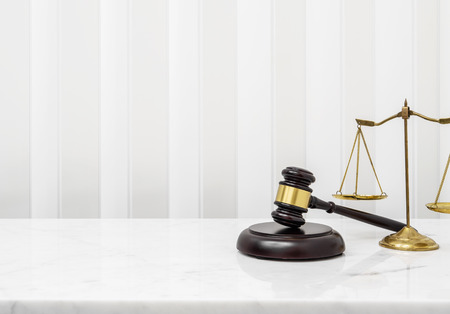 Wooden gavel and lawyer balance scales on white marble counter table top.