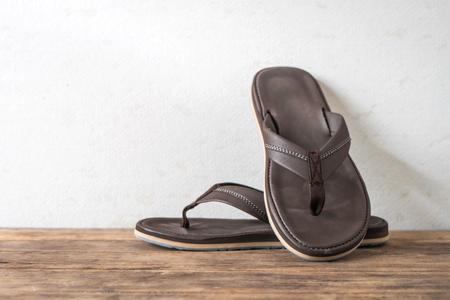 Men sandals footware brown on wood grunge table desk with copy space. Zdjęcie Seryjne