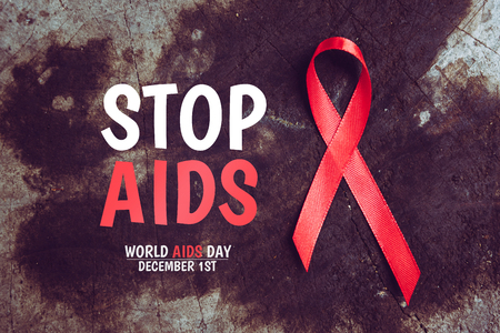 Stop aids text with red ribbon symbol of human immunodeficiency virus disease. dark background. aids concept. Stock Photo