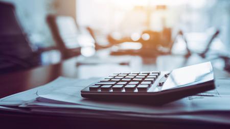 Close up calculator on business working desk, dark background concept. Banco de Imagens