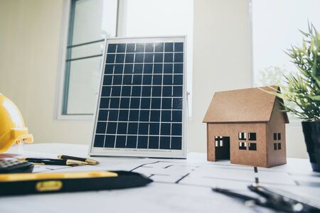 Desk of architects Solar Energy Powered Home Green for reduce global warming concept. Banco de Imagens