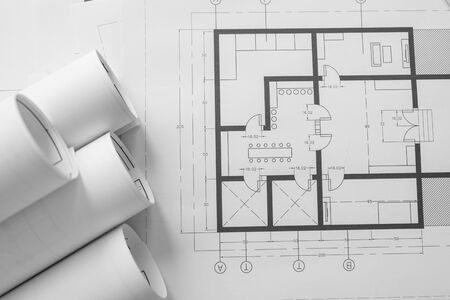 Architect house plan roled -up plans on the table, high angle view and engineer object. Stock Photo
