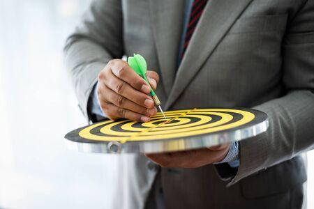 Business man poiting to center of dartboard for aspiration concepts. Banco de Imagens