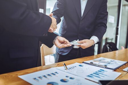 Shaking hands working together two business man while pay banknote in modern office.