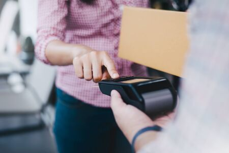 Young woman uses a credit card to pay for goods, NFC payment concept with delivery service. Stockfoto