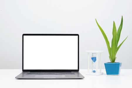 Mock up laptop with blank screen and plant with sandglass for display banner or advertise.