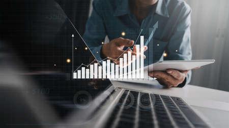 Business investor analyzing business intelligence (BI) with key performance indicators (KPI), profit increase, using tablet and laptop.