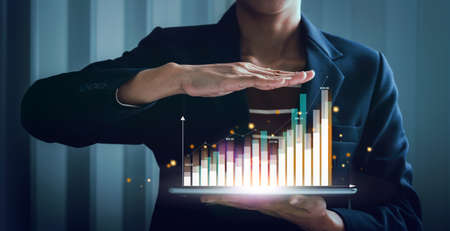 Business woman trader holding tablet analyzing digital stock market virtual hologram with growth graph chart progress, trading cost planning and strategy buy and sell. Фото со стока