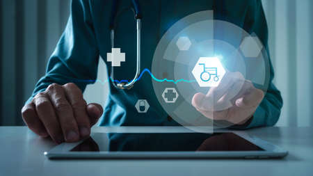 Medical doctor touching wheelchair icon with AI technology, virtual interface of disability. Фото со стока