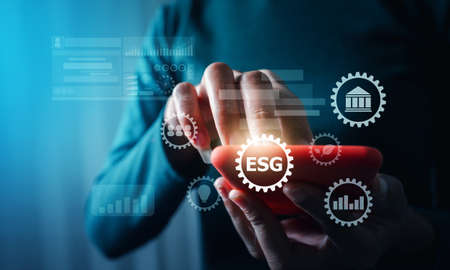 Business woman with ESG environment green business concept, hand holding mobile gear virtual reality of environment social governance concept. Фото со стока