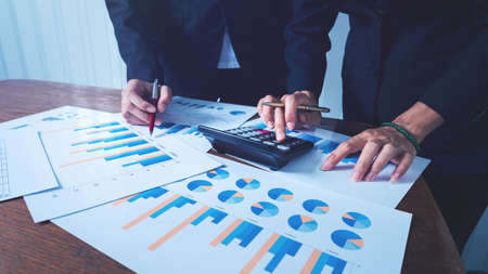 Working together business women with financial charts and graph with calculator for calculating data and management.