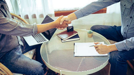 Colleagues, business men discuss work with each other while sitting in a coffee shop, Shaking hands shot.