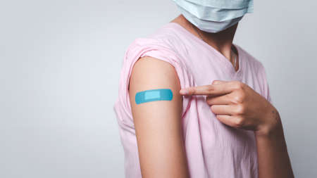 Young woman pointing adhesive bandage on her arm after injection of vaccine. Фото со стока