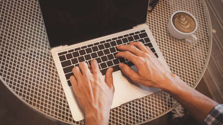 Close up hands of business man using laptop with coffee cup on table, high angle view.