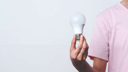 Close up hand of woman holding light bulb with copy space.